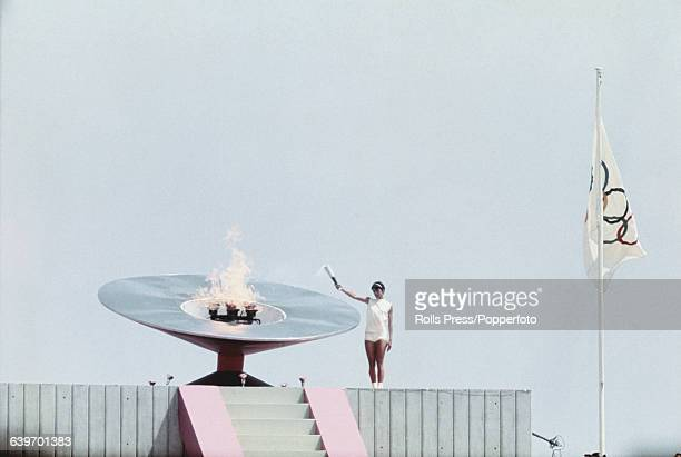View of Mexican athlete Enriqueta Basilio holding out the Olympic torch to light the Olympic Cauldron inside the Estadio Olimpico during the opening...
