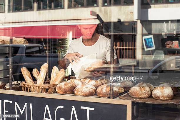 View of mid adult male owner working at bakery through display cabinet