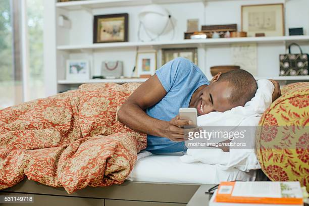 View of mid adult man using cell phone in bed