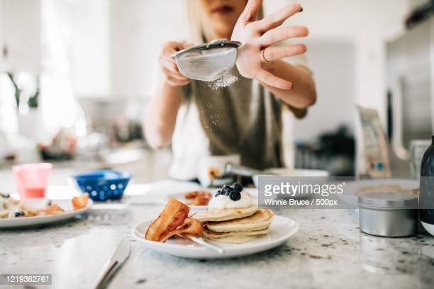 view of mid adult woman preparing pancakes in kitchen - differential focus stock pictures, royalty-free photos & images