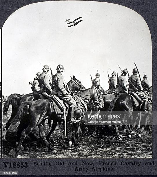 View of military scouts, old and new, the French cavalry gaze up at an Army airplane flying overhead,