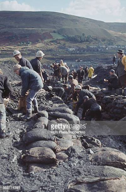 View of miners and rescue volunteers clearing and stabilising the colliery spoil tip above the village of Abefan in Wales following its collapse and...