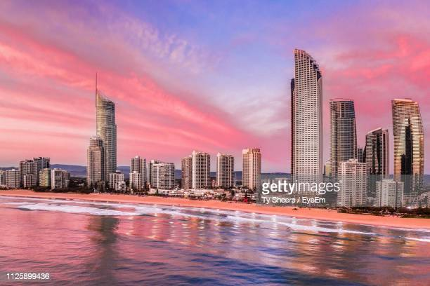 view of modern buildings by sea against sky during sunset - gold coast queensland stock pictures, royalty-free photos & images