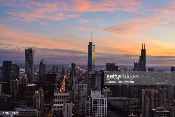 View Of Modern Cityscape Against Cloudy Sky During Sunset