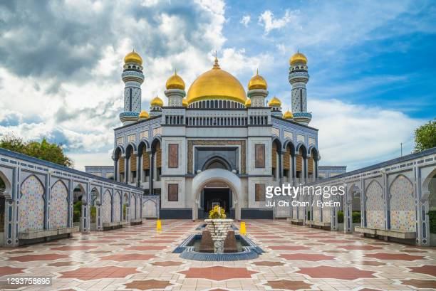 view of mosque against cloudy sky - brunei stock pictures, royalty-free photos & images