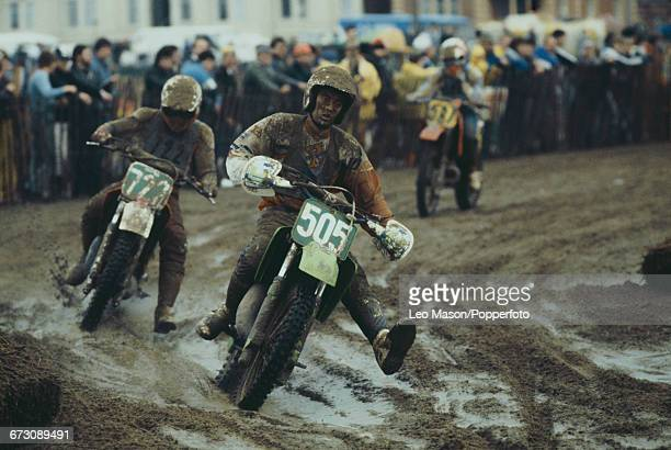 View of motocross competitors covered in wet sand during competition in the Weston Beach Race event held on a beach at WestonsuperMare in Somerset...