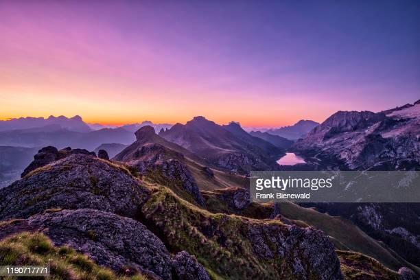 View of mountainous dolomiti landscape around Fedaia Lake, Lago di Fedaia at sunrise, the Setsas mountains in the distance, from a hill above Pordoi...