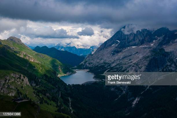 View of mountainous dolomiti landscape around Fedaia Lake, Lago di Fedaia, and the summit of Marmolata, Marmolada covered in clouds.