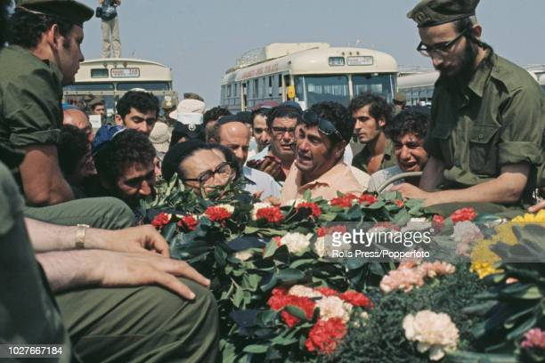 View of mourners crowding around members of the Israel Defense Forces seated in the rear of military trucks each containing a flower covered coffin...