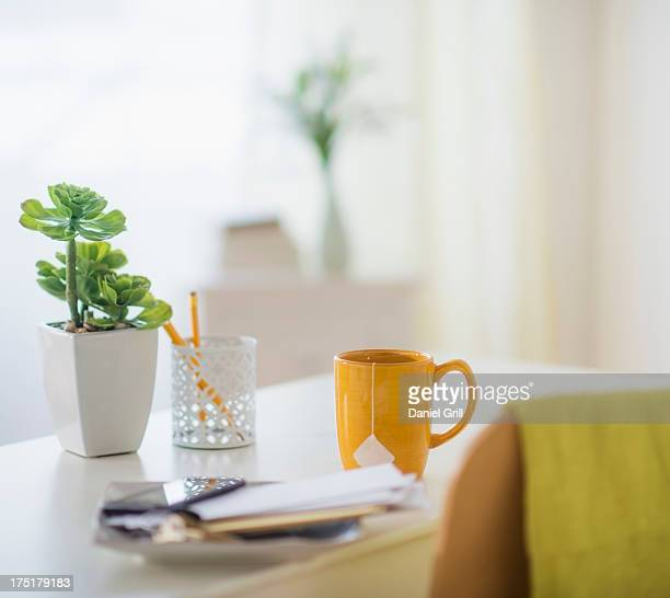 View of mug, flower pot, mobile phone and paper on table