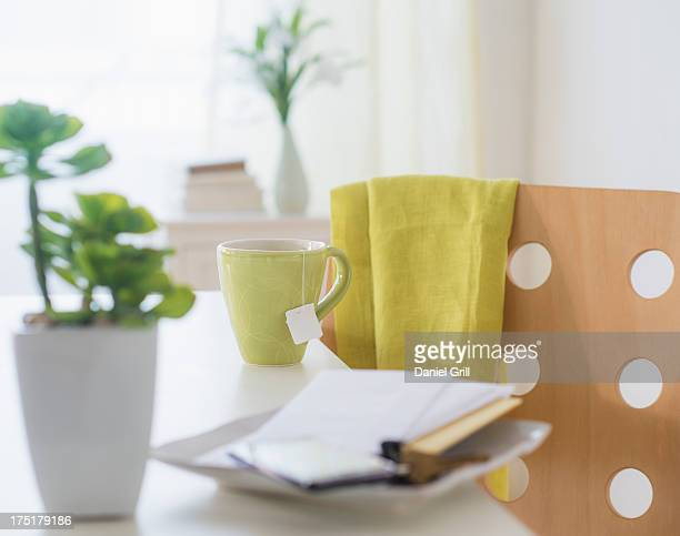 View of mug, flower pot, mobile phone, key and paper on table