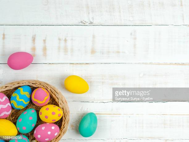 view of multi colored easter eggs in wicker basket - easter stock pictures, royalty-free photos & images
