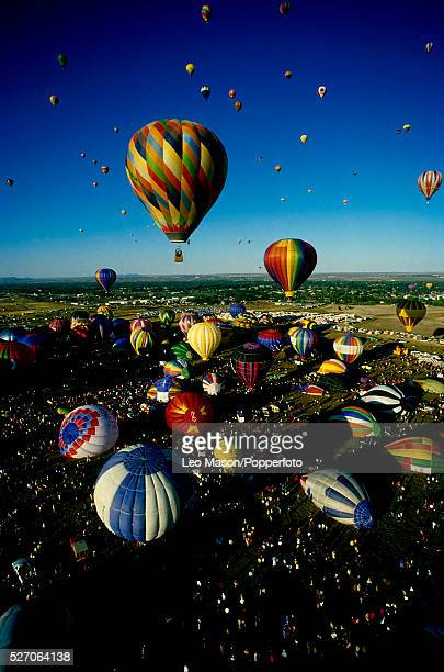 View of multiple hot air balloons being prepared for flight and lifting off in to the air during the Albuquerque International Balloon Fiesta in...