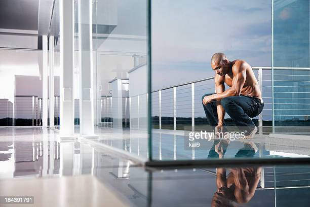 View of muscular African American man junto a la piscina