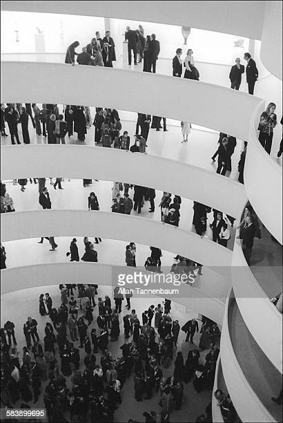 View of museum attendees in the spiral galleries of the Guggenheim Museum at the opening of an exhibit of works by Max Ernst, New York, New York,...