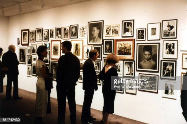 View of museum goers as they look at a wall of Bruce Weber's photographs on display during the Whitney Biennial New York New York April 9 1987