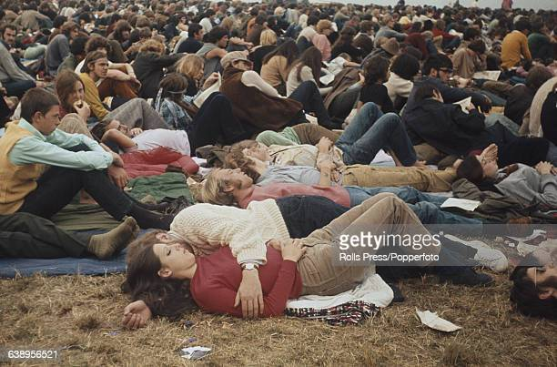 View of music fans, festival goers and visitors to the 1969 Isle of Wight Pop Festival lying down and sitting in a large field on site to listen to...