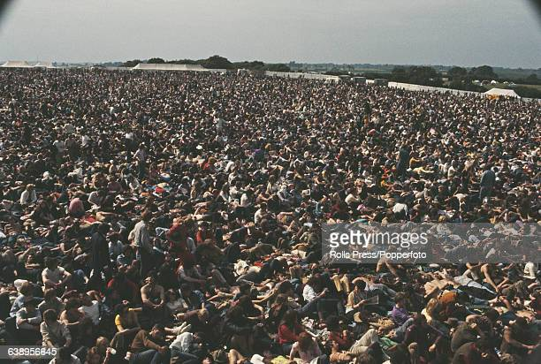 View of music fans festival goers and visitors to the 1969 Isle of Wight Pop Festival part of an estimated 150000 audience standing and sitting in a...