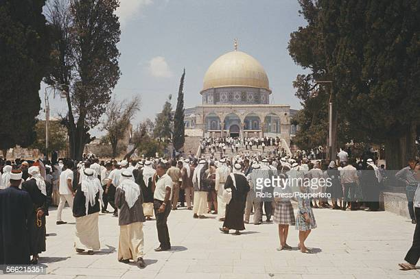 View of muslim men women and worshippers congregating for Friday prayers on steps and under arches in front of the Dome of the Rock shrine in the old...