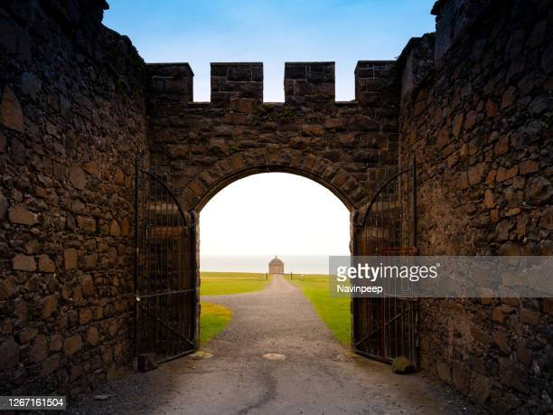 view of mussenden temple from downhill demesne's large masonry gateway - castle stock pictures, royalty-free photos & images