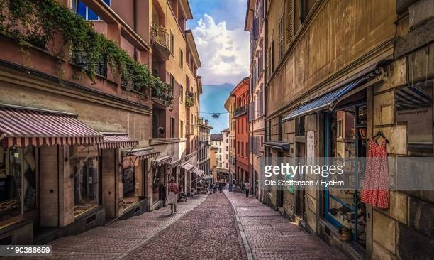 view of narrow alley amidst buildings in city - スイス ルガーノ ストックフォトと画像