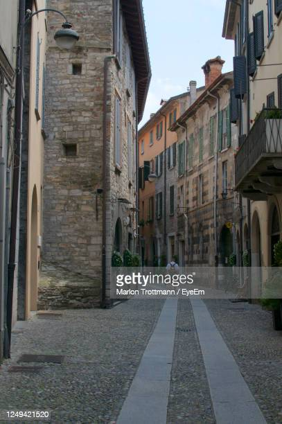 view of narrow pedestrian alley surrounded by beautiful houses in the city of como, lombardy - コモ ストックフォトと画像