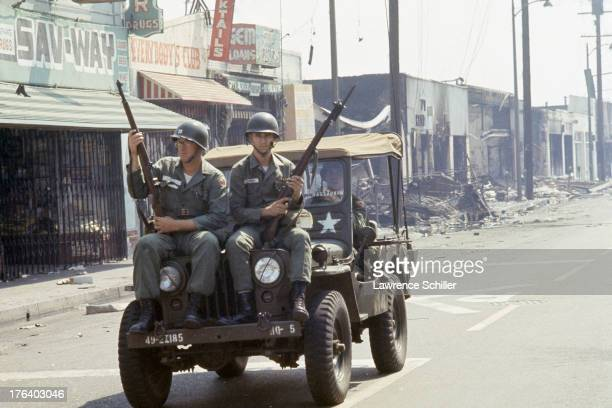 View of National Guardsmen on a Jeep as they patrol the streets of the Watts neighborhood after the declaration of Marshall Law due to ongoing riots...