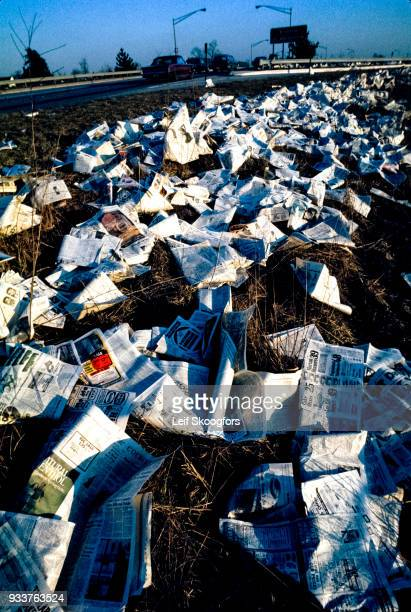 View of newspaper litter along a highway 1999 The highway sign in the background shows exits for Trenton New Jersey and Delaware Memorial Bridge