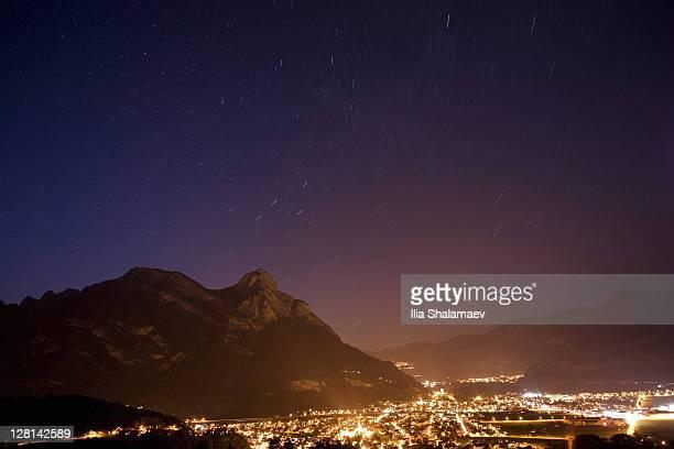 View of night sky and star trails over Rhein valley that separates Liechtenstein and Switzerland
