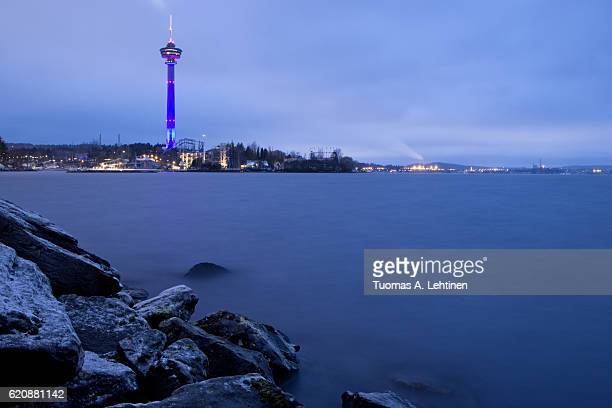 View of Näsinneula observation tower, lake and rocky shore in Tampere, Finland, in the evening.