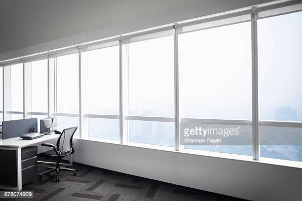 view of office desk next to bright windows - 窓 ストックフォトと画像