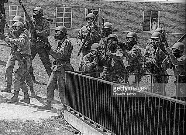 View of Ohio National Guardsmen in gas masks as they aim their weapons on the Kent State University campus during student antiwar protests Kent Ohio...