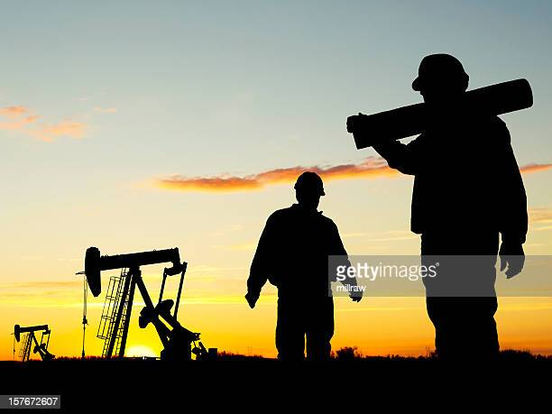 A view of oil workers at Well Pumpjack Site at dusk
