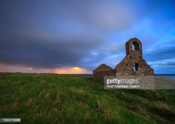 view of old church against cloudy sky - isle of man stock pictures, royalty-free photos & images