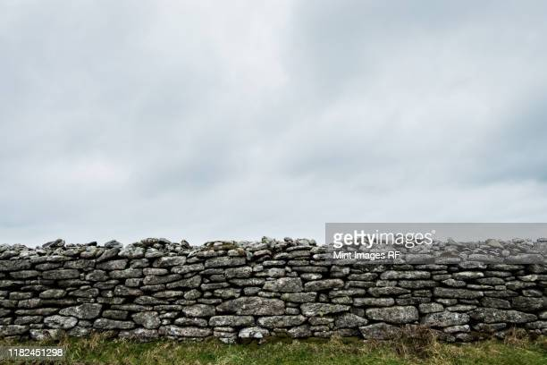 view of old dry stone wall under a cloudy sky. - stone wall bildbanksfoton och bilder