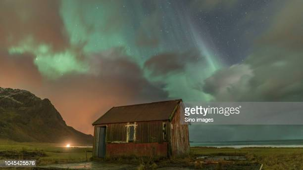 view of old hut against northern lights, norway - image stockfoto's en -beelden