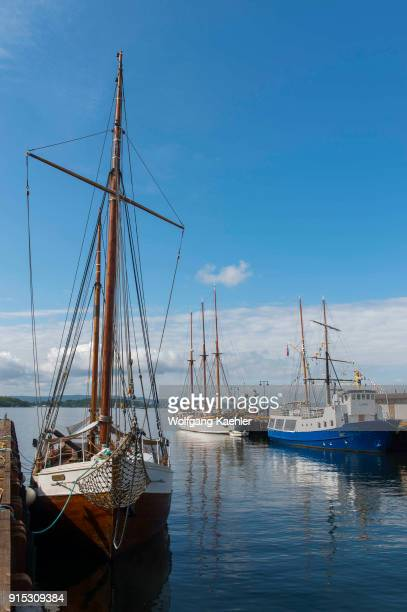 View of old sail boats docked in the harbor in front of the city hall in Oslo Norway