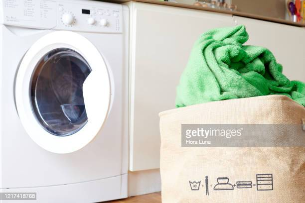 view of old-style laundry basket with green blanket and open washing machine - blanket stock pictures, royalty-free photos & images