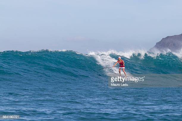 View of one girl in Santa Claus outfiti paddling on a stand up paddle board on a big waves, Fuerteventura. Spain