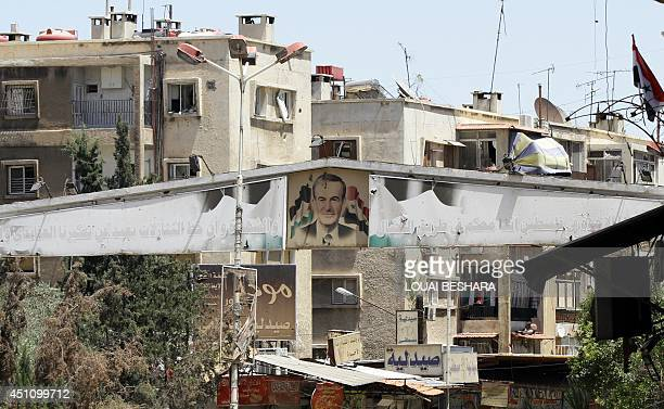 A view of one of the entrances to the Yarmuk Palestinian refugee camp in Damascus decorated with a poster of late Syrian leader Hafez alAssad on June...