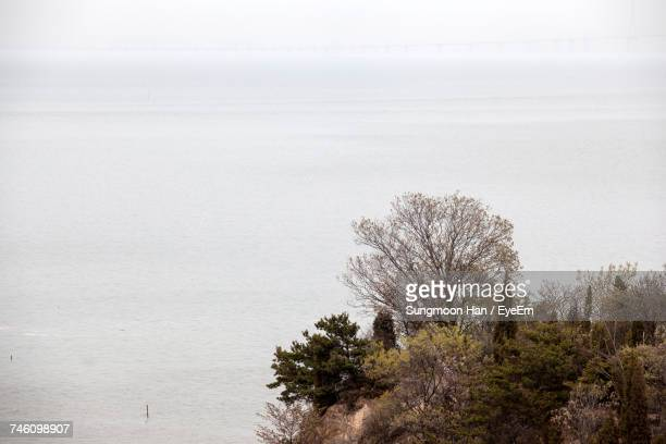 view of overcast sky blending into seascape in autumn - incheon stock pictures, royalty-free photos & images
