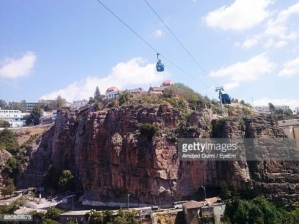 View Of Overhead Cable Car And Buildings On Rock Against Cloudy Sky