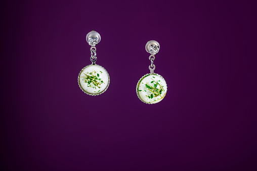 View of pair of earrings on purple background - gettyimageskorea