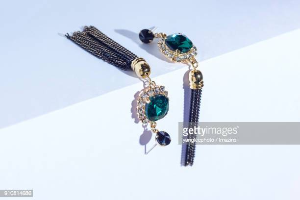 view of pair of earrings on purple background - earring stock photos and pictures