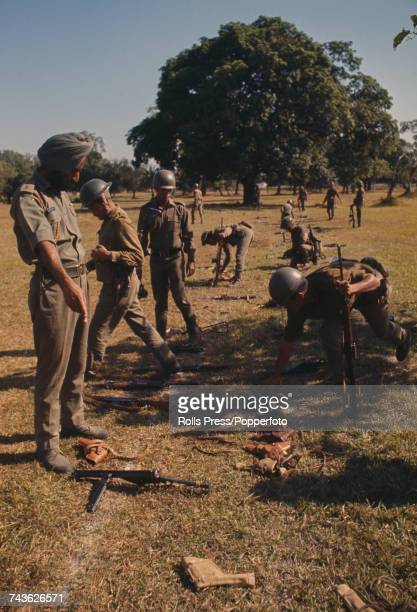 View of Pakistan Army troops laying down their arms on the ground as Indian Army soldiers bend down to pick them up during a disarming ceremony in...