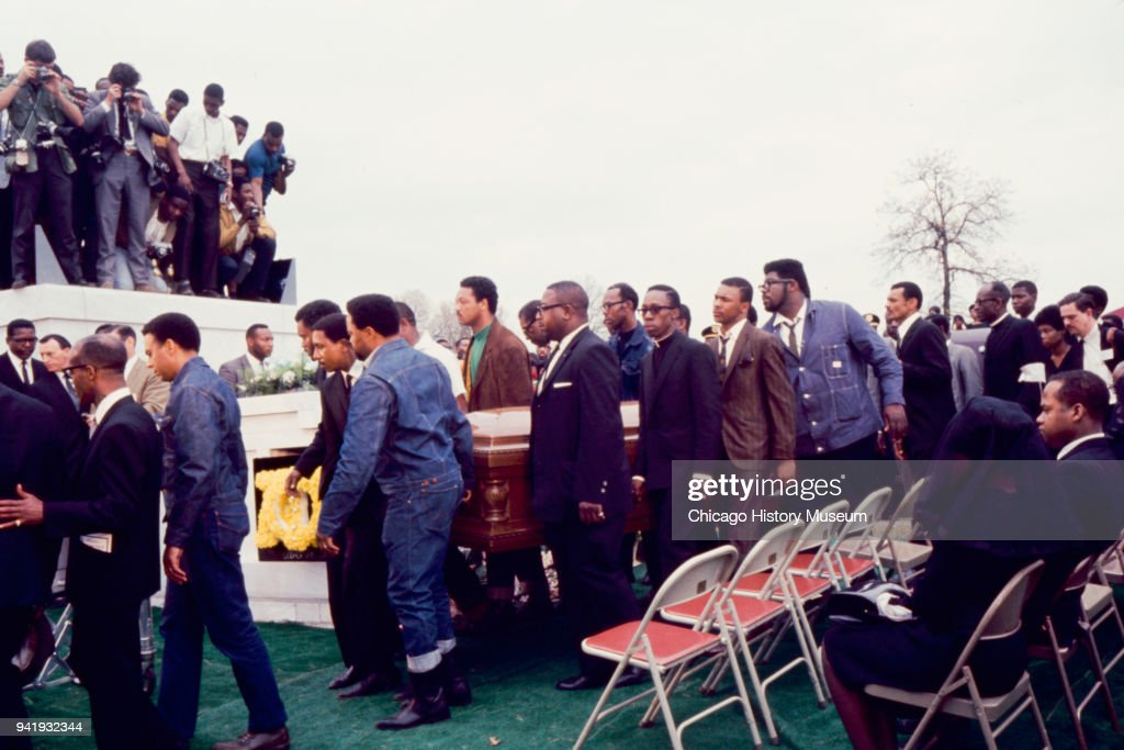View of pallbearers, among them Civil Rights leader Jesse Jackson (in green shirt) as they Dr Martin Luther King Jr's casket during his burial service at South View Cemetery, Atlanta, Georgia, April 9, 1968. Also visible is fellow Civil Rights activist Andrew Young (second left, in denim jacket and brown shoes).
