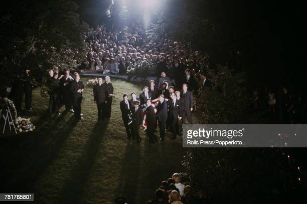 View of pallbearers carrying the casket containing the body of assassinated Senator Robert F Kennedy across grass to the burial site in Arlington...