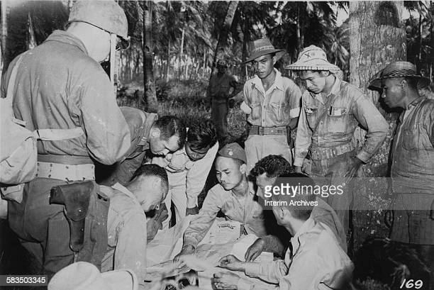 View of Panay guerilla leaders huddled around a map while in conference with American Division G2 soldiers Panay Philippines 1940s