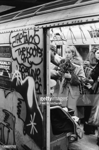 View of passengers through the open door of a crowded graffiticovered subway car New York New York February 25 1977
