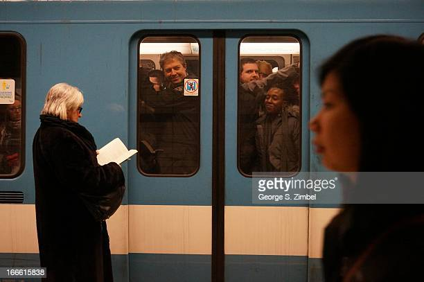 View of passengers visible through the doors of a crowded Metro train as other commuters wait on the platform Montreal Quebec Canada 2013